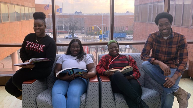 Students sitting with books smiling.