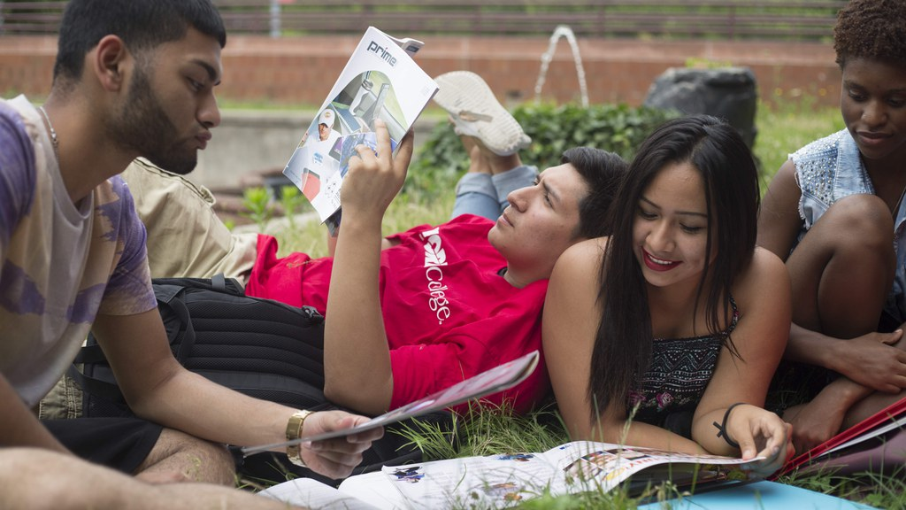 Picture of students on the grass reading.