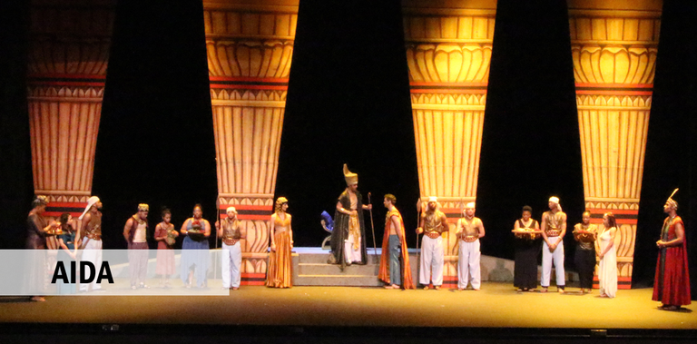 Cast members in ancient Egyptian costumes stand in front of four towering columns.