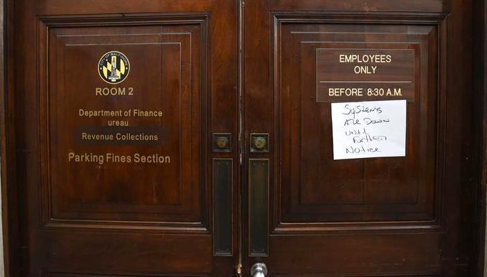 Image of entrance to Baltimore Department of Finance and Revenue Collections with a systems all down notice on the door.