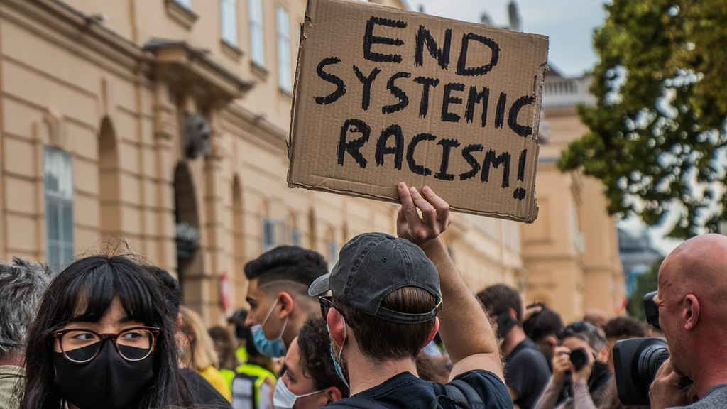 "The person holding a sign that reads ""end Systemic Racism"""