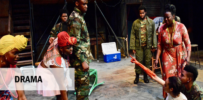 Scene from Ruined by Lynn Nottage with bloodied woman pointing up at soldier.