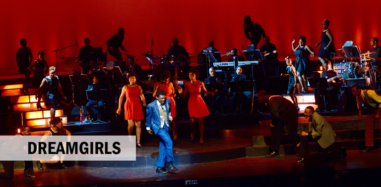 Picture of man with blue suit dancing in front of three Dreamgirls dressed in red all in front of large band with red backdrop.