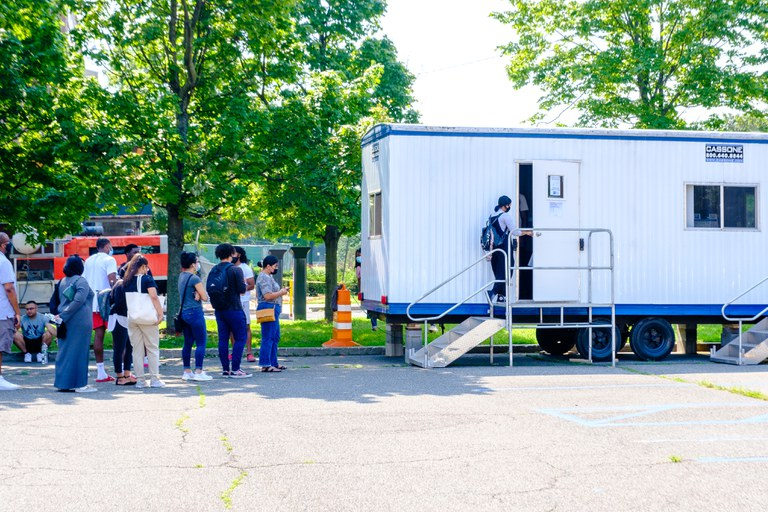 A student entering the COVID-19 testing trailer on campus, others waiting inline