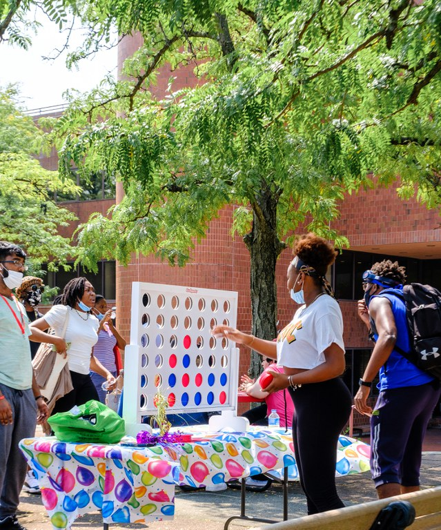 Students playing connect four in a row outdoors