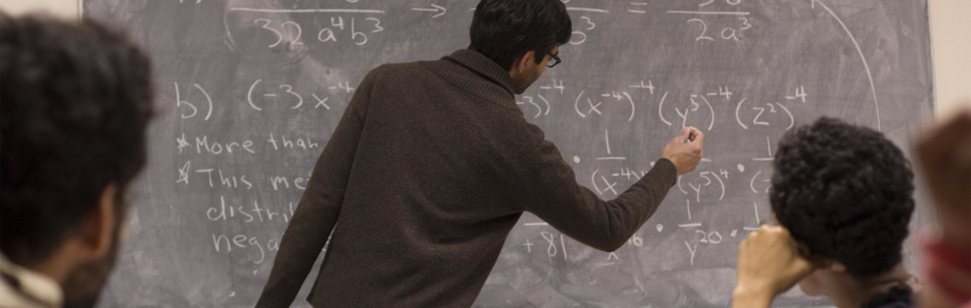 Graduate Student writing a formula in the blackboard