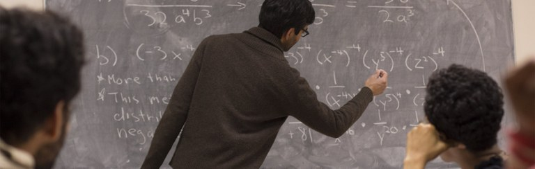 Graduate Student writing a formula in the blackboard
