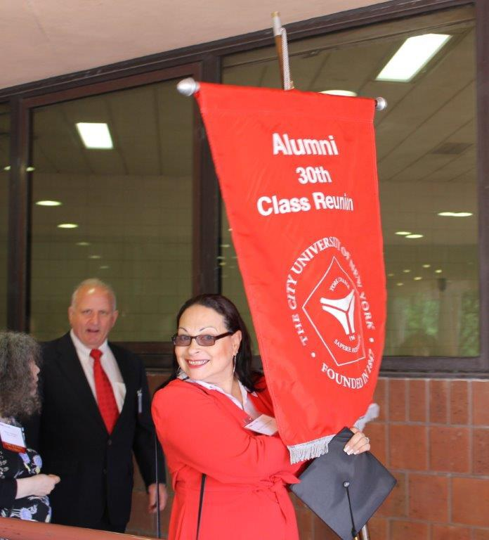 Alum Brunilda Almodovar holding her class banner