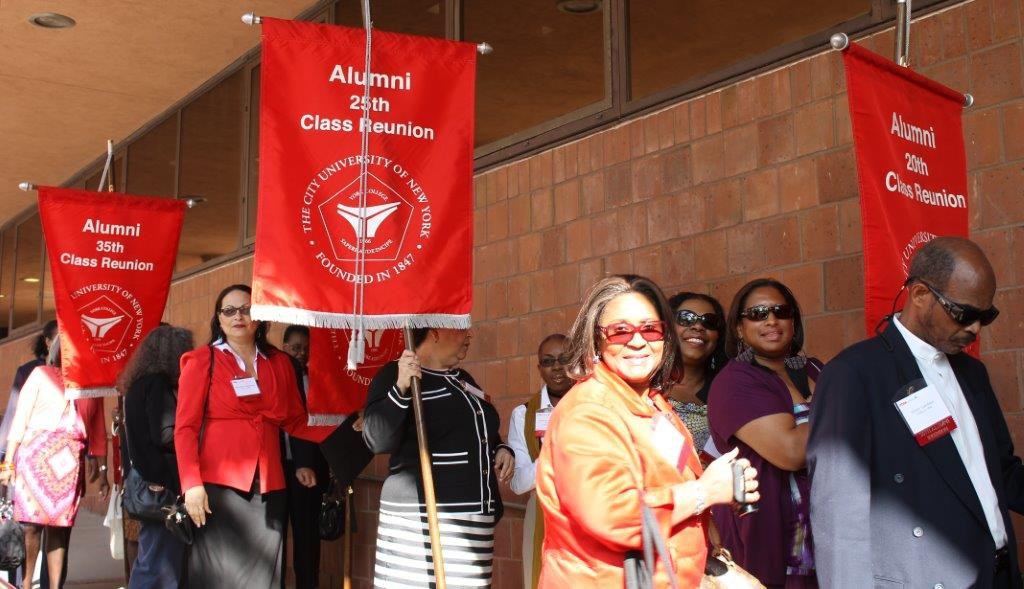 Alums walking with their Class banner