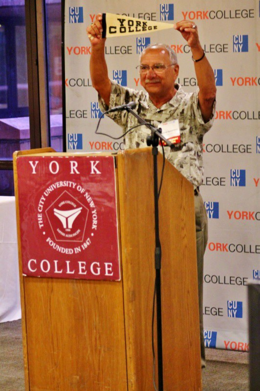 Alumni holding up his old York college banner