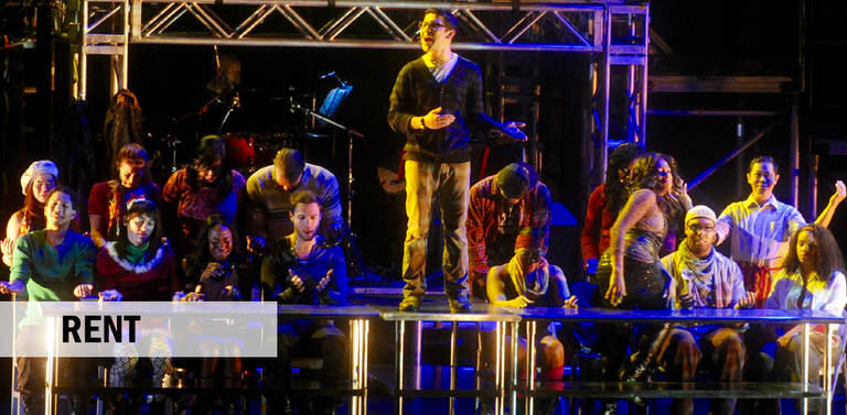 Singer standing on top of long metal table surrounded by others lit in blue light.