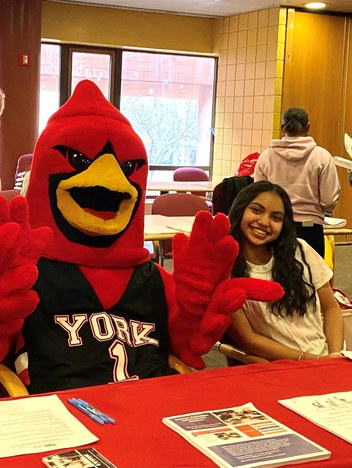 Student at an open house with mascot