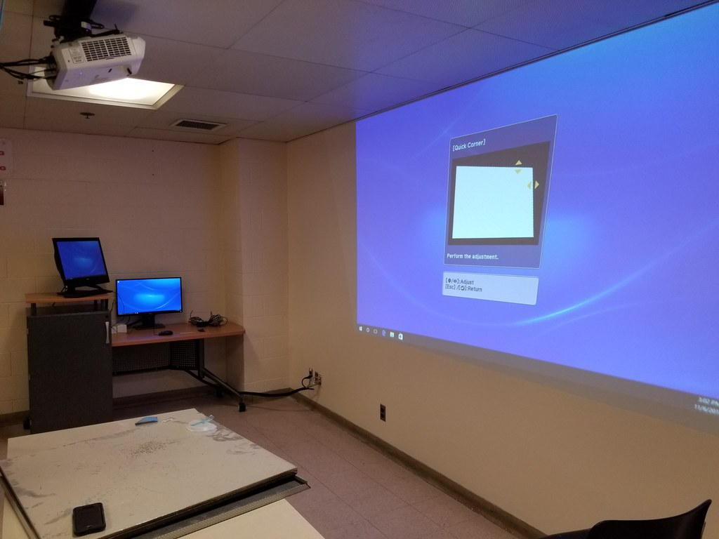 A picture of a class room with a projector, lectern, a projection screen and a computer.