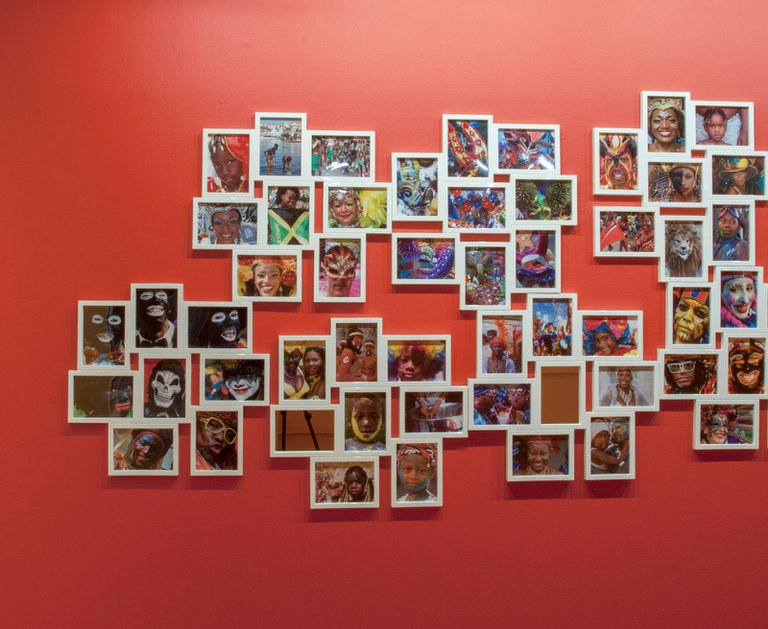 large number of small photographs as installed in a cluster in the gallery, left portion
