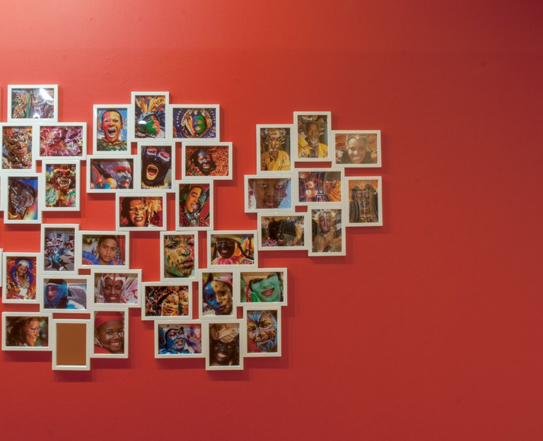 large number of small photographs as installed in a cluster in the gallery, right portion